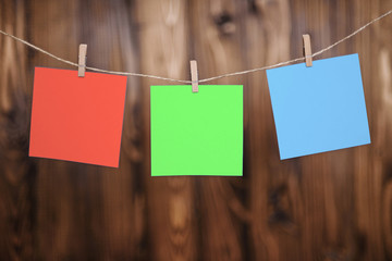 Close up of three red yellow and blue note papers hung by wooden clothes pegs on a brown wooden background
