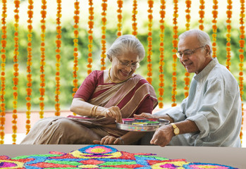 Old couple making a rangoli