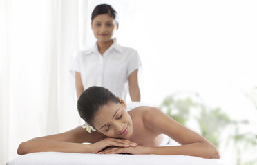 Young woman lying on massage table with massage therapist in the background