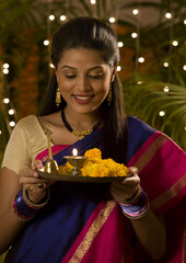 Woman holding a tray with a diya