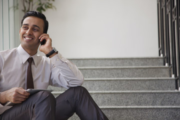 Male executive with tablet talking on a mobile phone