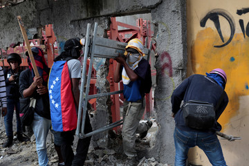 Demonstrators collect materials to build barricades while rallying against Venezuela's President Nicolas Maduro's government in Caracas