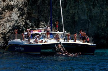 Tourists swim off the sailing catamaran 'Spirit of Malta' at Comino, the smallest of the three inhabited islands that make up the Maltese archipelago