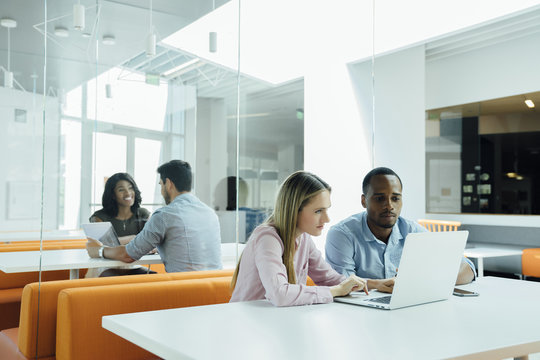 Coworkers meeting in groups in modern office space