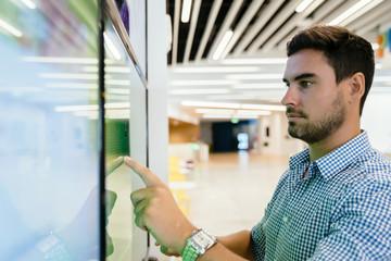 Man touching large computer screen monitor