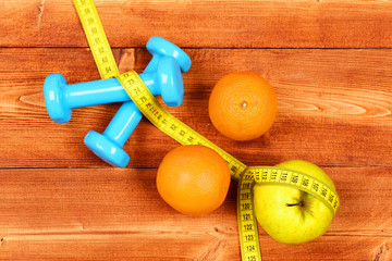 fruits with dumbbells weight and measuring tape on brown vintage