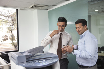Two male executives looking at an sms on a mobile phone