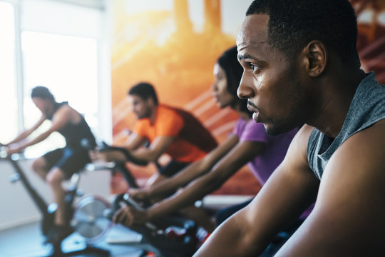Group of people cycling in spin class at gym