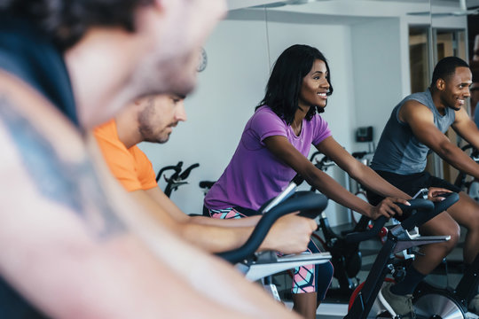 People cycling in a spin class at a gym