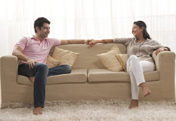 Full length of smiling young couple holding hands on sofa