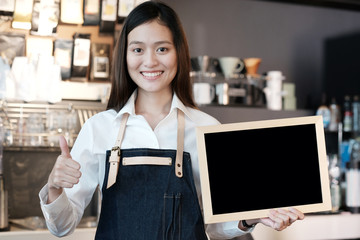 Young asian women Barista holding blank chalkboard and thumb up gesture with smiling face in font of cafe counter background, small business owner, food and drink industry concept
