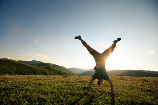 handstand woman in a sunset mountain top grassland meadow