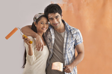 Portrait of cute young couple smiling while painting their house