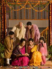 Family arranging diyas
