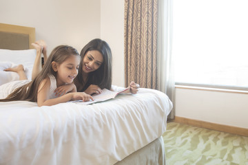 Mother and daughter lying on bed reading picture book