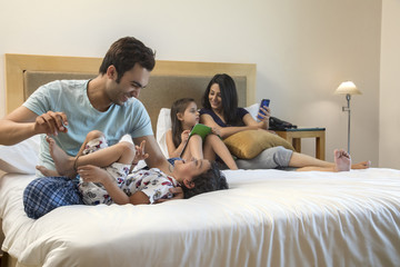 Family in bedroom focus on father and son playing while mother and daughter using phone