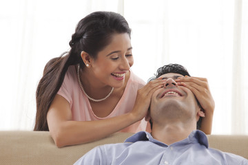 Beautiful young woman covering man's eyes at home
