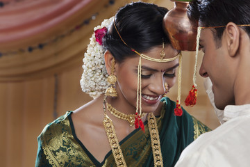 Maharashtrian bride and groom performing a ritual