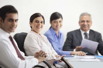 Portrait of mature businesswoman smiling with other executives