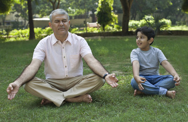 Grandfather meditating while grandson looks on