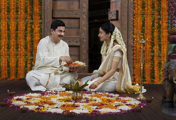 South Indian couple with a flower rangoli