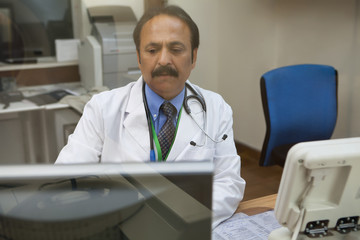 Doctor looking at CT scan on computer screen