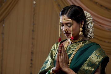 Beautiful young bride praying with eyes closed
