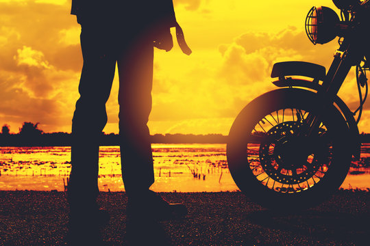 Silhouette of biker man with his motorbike beside the natural lake and beautiful, enjoying freedom and active lifestyle, having fun on a bikers tour.sunset background and sky.