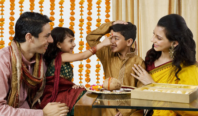 Girl putting a tikka on her brothers forehead