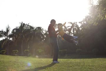 Grandfather swinging his grandson