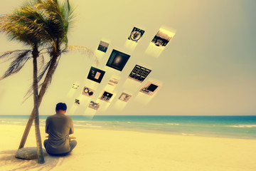A man working on the beach and uploading his pictures to Stock photos.