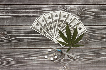 Marijuana, syringe, tablets of dollar bills on the background of a wooden table. Sale, use, distribution.