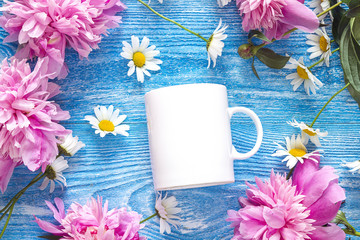 White coffee mug with chamomile flowers and pink peonies on blue wooden background.