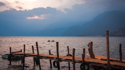 Boardwalk over Lake Atitlan on the shore of Panajachel village in Guatemala at sunset with some kayakers in mid-ground.