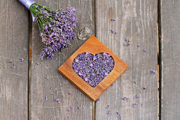 Lavender in wooden heart-shaped box and bunch of lavender flowers on wooden background
