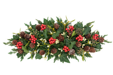 Christmas and winter decoration with holly, ivy, mistletoe, fir and pine cones on white background.