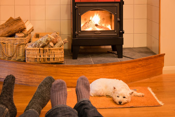 Socks and feet of a couple relaxing by fire in woodburner with west highland terrier - focus is on dog and stove