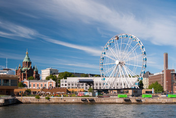 View of Helsinki harbor with Uspensky orthodox cathedral and a skywheel during a summer afternoon