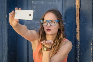 Young female taking selfie in front of old door