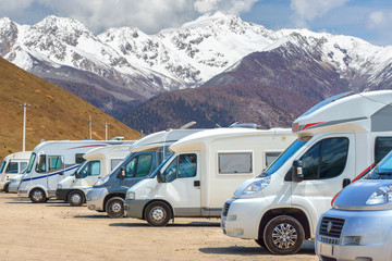 Close up motorhomes parked in a row on background snow mountain nature landscape.