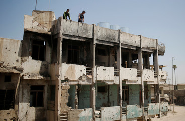 Iraqis stand on the roof of a destroyed building in western Mosul Iraq