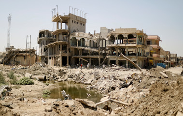 Iraqis pass destroyed buildings in western Mosul