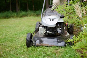 Man handling lawn with lawnmower.