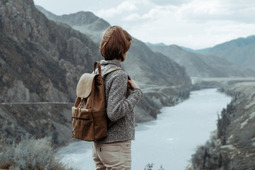 Hipster young girl with backpack enjoying mountain. Tourist traveler on background view mockup