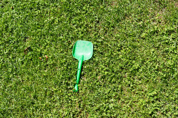 green kids shovel laying in the grass