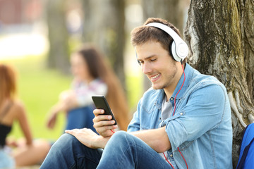 Student listening music with headphones in a park