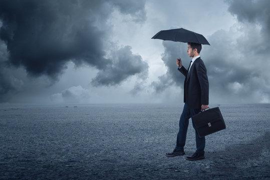 businessman below storm with umbrella