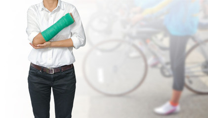 Female patient wearing white shirt with green cast on arm isolated on blurred background woman riding a bicycle, body injury concept