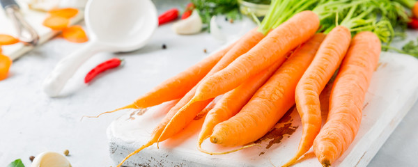Fresh carrots vegetables, spices and herbs for cooking soup on old white wooden cutting board with space for text. Healthy food ingredients.