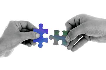 Zwei Hände halten Puzzleteile gegeneinander